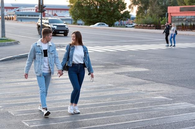 男と女は手をつないで、交差点に沿って道路を横断します。路上でのデート