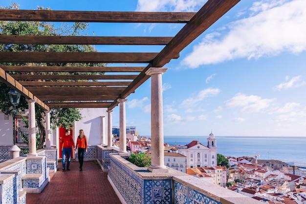 手をつないで歩いている男と女。街と海を見下ろす展望台。木造建築とポルトガルのタイル。