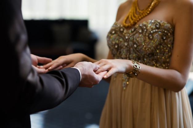 Парень и девушка в красивой одежде, взявшись за руки.