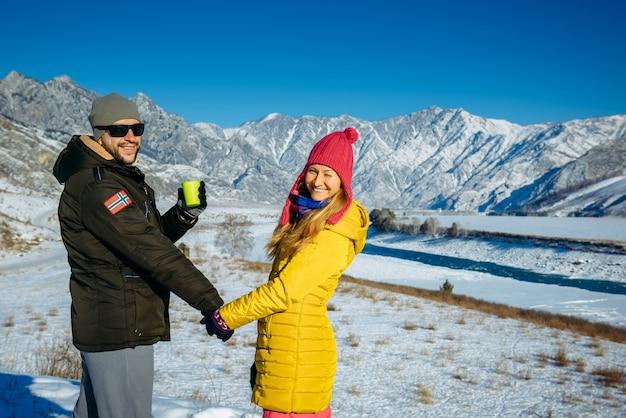 Парень и девушка в ярких одеждах, взявшись за руки, глядя на камеру и улыбается