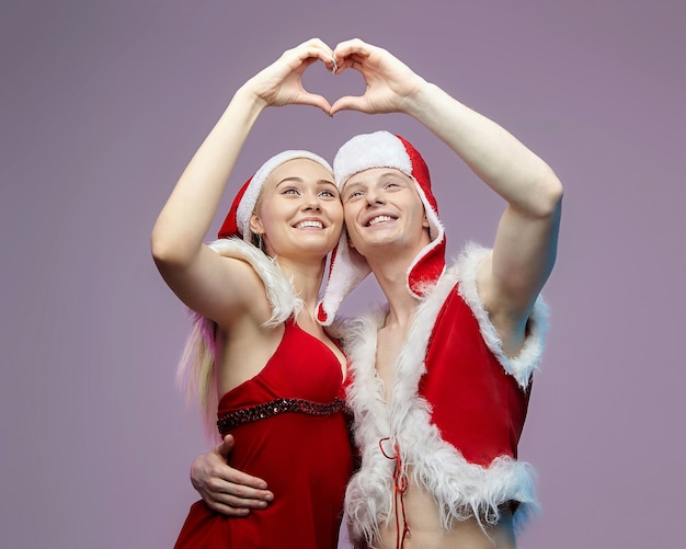サンタの衣装を着た男と女は、ハートの形に手を組んだ。クリスマスと新年のコンセプト