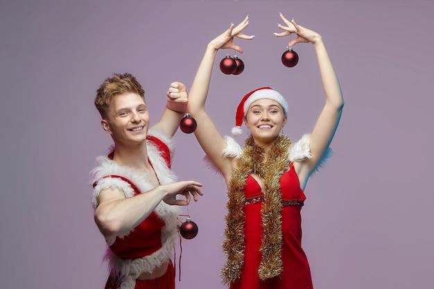 スタジオでの写真撮影でサンタの衣装を着た男と女。男は女の子にクリスマスの飾りを付けます