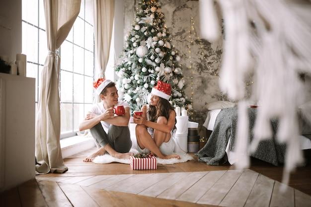 흰색 티셔츠와 산타클로스 모자를 쓴 남자와 여자는 새해 나무, 선물, 양초 옆 창문 앞 바닥에 빨간 컵과 함께 앉아 있습니다.