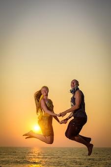 男と女が海を背景に空中ジャンプ。若い幸せなカップルは夕暮れ時のビーチでジャンプします