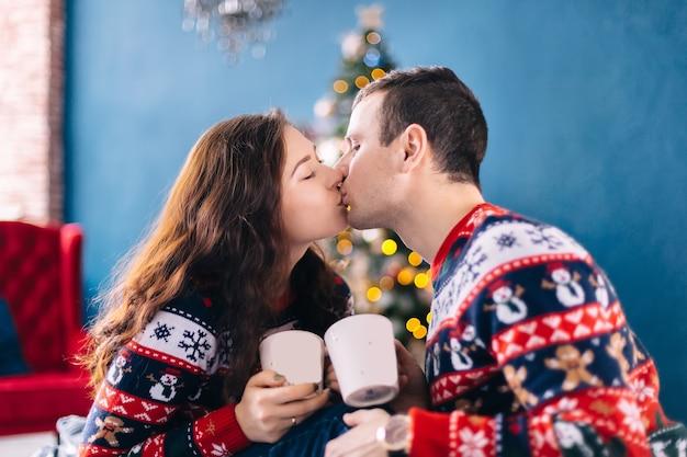 Парень и девушка целуются и держат чашку с горячим напитком в уютной комнате с елкой и креслом
