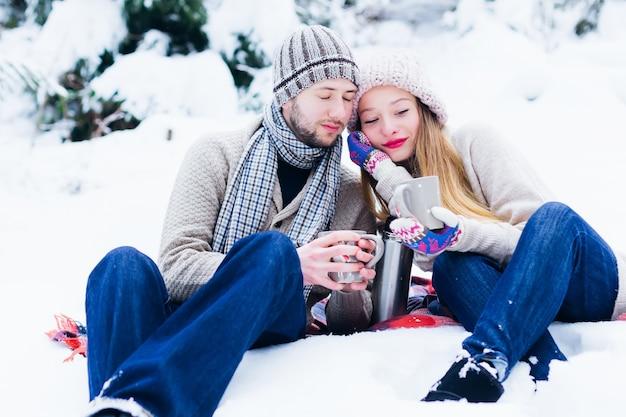 男と女は雪の中で座ってカップを手に持ってお互いに寄りかかった