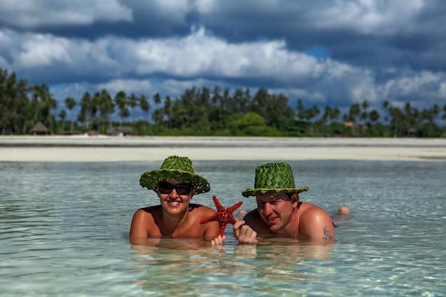 男と女は水のビーチに横たわっています