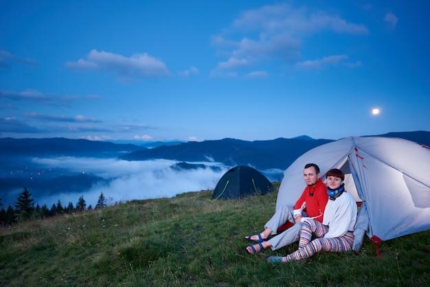 Парень и женщина в палатке на рассвете
