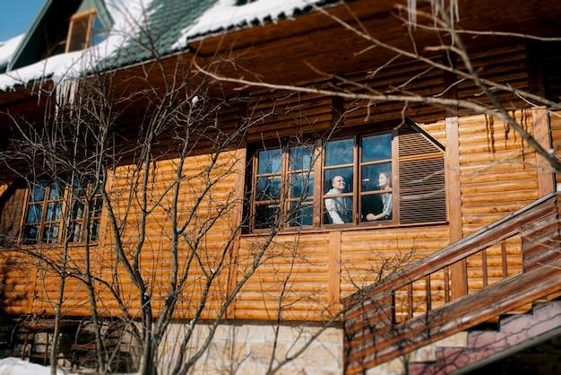 눈 덮인 풍경이 내려다 보이는 창 근처 집에있는 남자와 여자