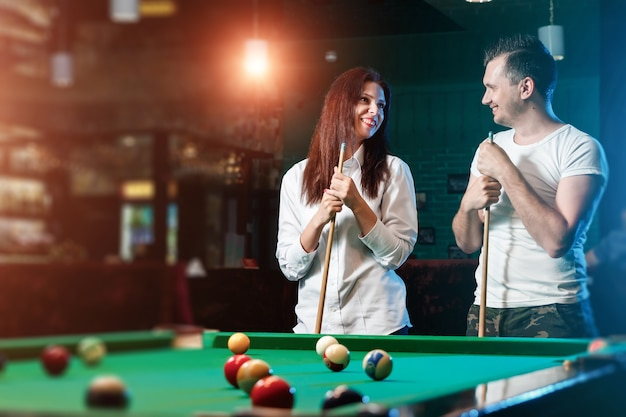 A guy and a beautiful girl are playing billiards, a guy is teaching a girl to play billiards