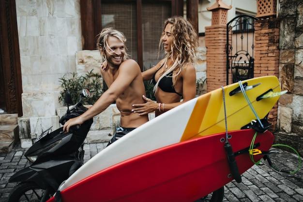バイクのハンドルを握っている男が笑っています。女性はバイクに座って男を抱きしめます。カップルはサーフィンに行きます