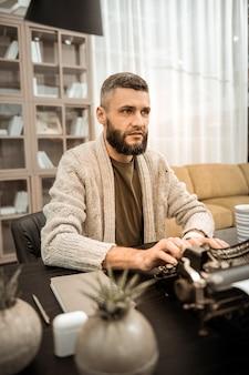 Парень занят. серьезный решительный старомодный мужчина печатает на редкой пишущей машинке, сидя в своем домашнем шкафу