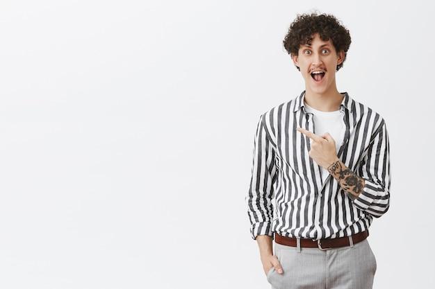 喜びと幸福から叫んで新しいタトゥーを作る前に興奮している男は面白がって立って、灰色の壁の上にポーズをとって左上隅を指している縞模様のクールなシャツに夢中