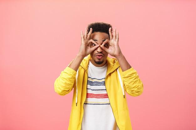 Il ragazzo impressionato non può credere ai propri occhi che gasano attraverso i cerchi fatti dalle dita alla telecamera eccitato e stupito in piedi su sfondo rosa in giacca gialla alla moda incuriosito e stordito.
