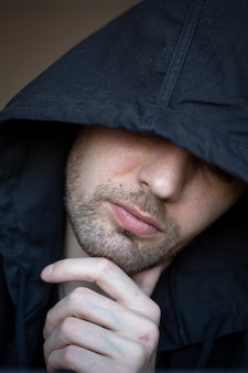 A guy in a black hood with a close-up portrait.