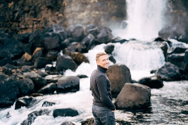 Guy in a black knitted sweater stands on rocks