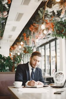 Ragazzo in abito nero. maschio al ristorante. uomo con un computer.