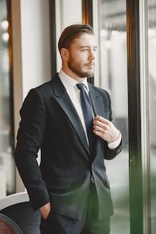 Ragazzo in abito nero. maschio al ristorante.