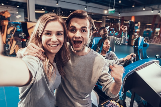 Guy and blonde girl in arcade. couple is taking selfie.
