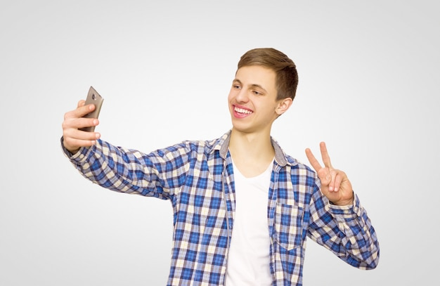 Guy in a blue shirt makes a selfie on the phone