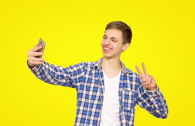 Guy in a blue shirt makes selfie on the phone