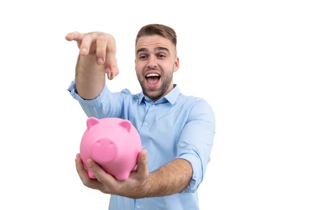 A guy in a blue shirt throws a coin into a pink piggy bank