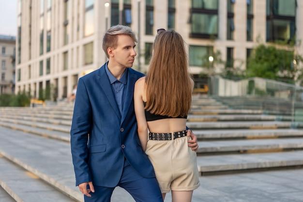 Guy in business suit hugs girl in shorts on street