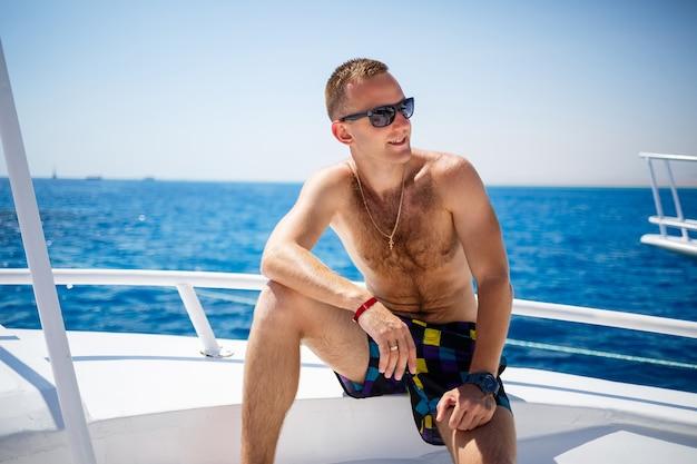 붉은 바다에서 흰색 요트에 반바지와 안경 남자 사업가