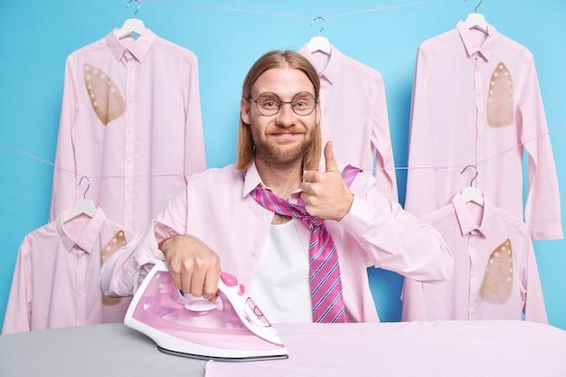 家で服にアイロンをかけるのに忙しい男は、ジェスチャーが丸い眼鏡を着ているように、親指を立てるショーをしている ネクタイの付いたフォーマルシャツは、青に隔離された電気機器を使う
