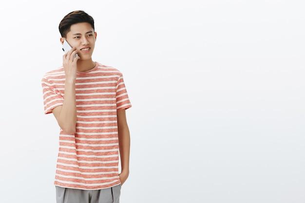 Парень звонит другу, небрежно разговаривает через смартфон, стоя слева от копировального пространства, глядя в сторону с красивой улыбкой, используя мобильный телефон для связи с семьей, живя за границей над белой стеной