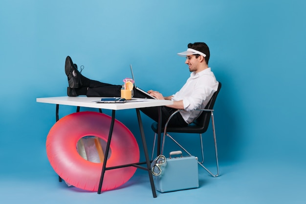 Guy in cap works with laptop, sitting with his legs thrown on table. portrait of man against space of suitcase and inflatable circle.