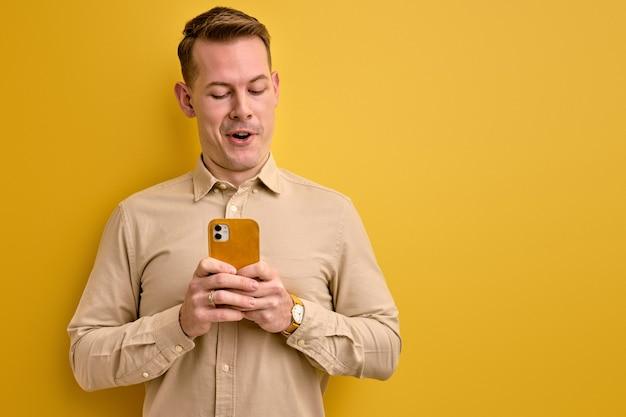携帯電話でチャットしている男は、メッセージの孤立した黄色の壁に感情的に反応します
