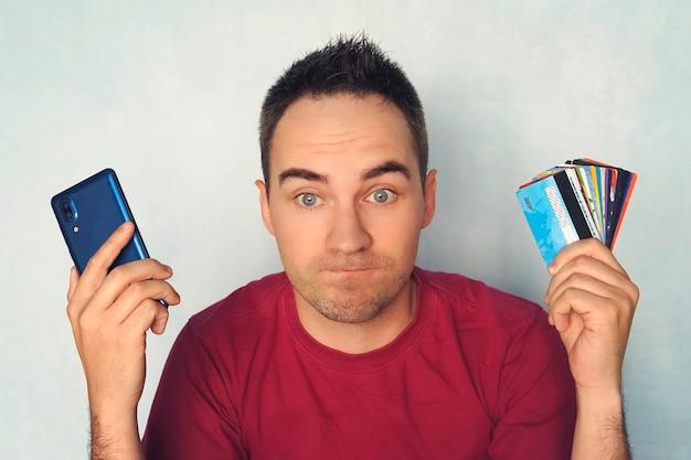 Guy는 지불할 신용 카드를 선택합니다. 휴대폰으로 결제할 때 남자의 얼굴에 당황. 손에 많은 플라스틱 카드. 은행 카드 서비스를 위한 휴대전화.