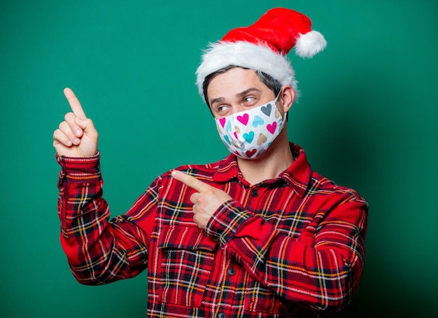 Guy in christmas hat and face mask on green