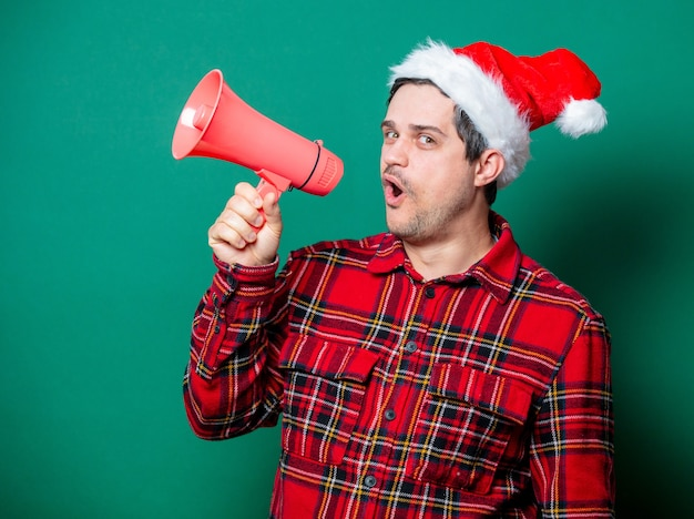 Guy in christmas hat and face mask with megaphone on green