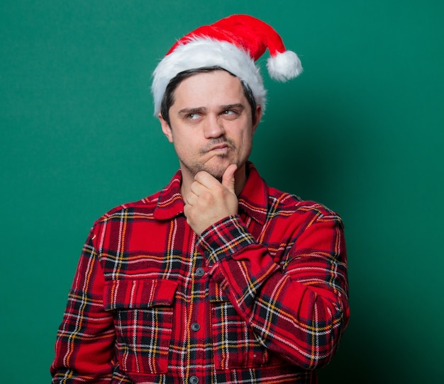 Guy in christmas hat and tartan shirt on green