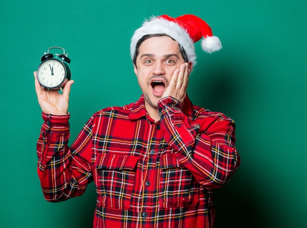 Guy in christmas hat and tartan shirt with alarm clock on green