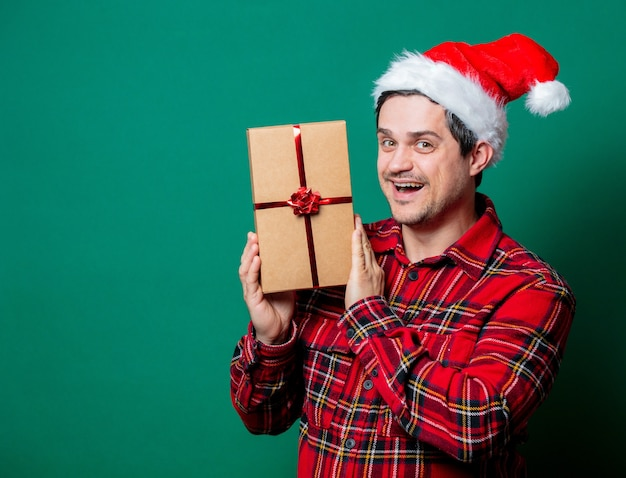 Guy in christmas hat and tartan shirt with gift box on green