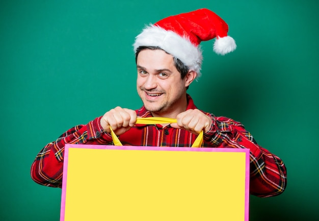 Guy in christmas hat and tartan shirt with shopping bag on green