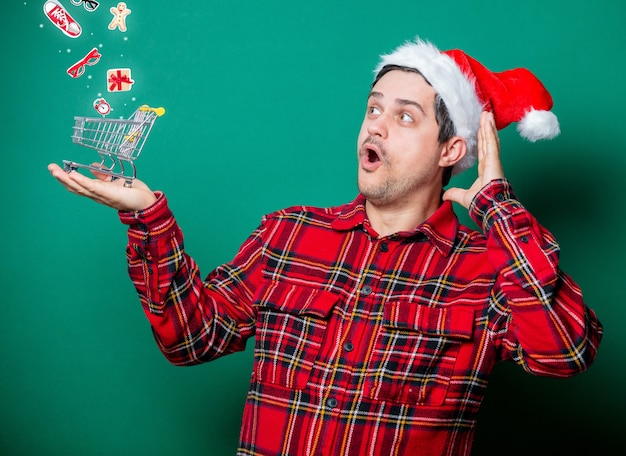 Guy in christmas hat and tartan shirt with shopping cart on green