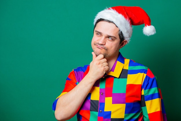 Guy in christmas hat and vintage shirt on green