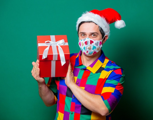 Guy in christmas hat and vintage shirt holding a gift on green