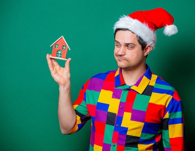 Guy in christmas hat and vintage shirt holding toy house on green