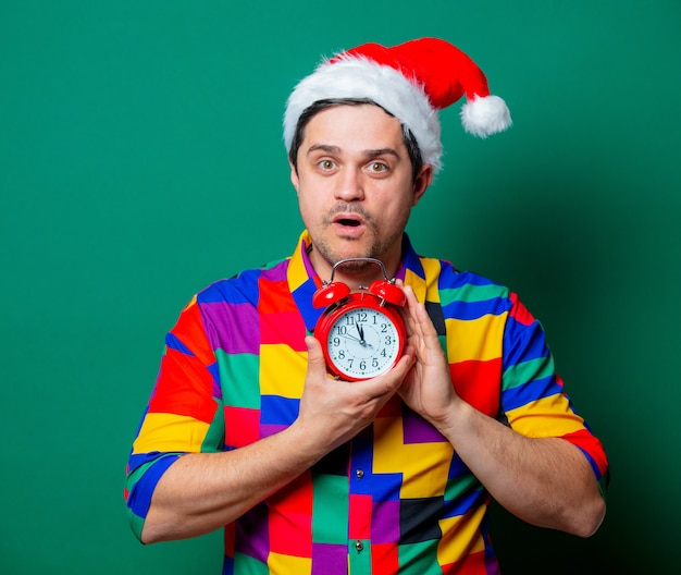 Guy in christmas hat and vintage shirt with alarm clock on green