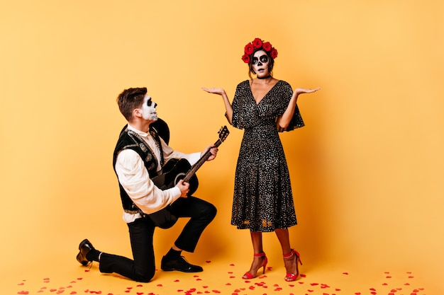 Guy in classic trousers sings serinade with guitar to his surprised girlfriend. full-length shot of models in love on isolated wall