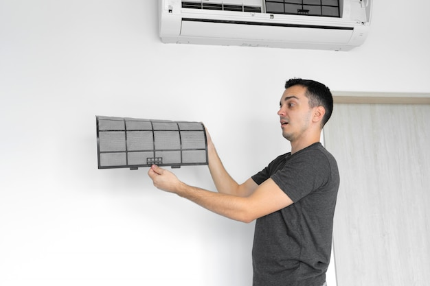 The guy cleans the filter of the home air conditioner from dust. very dirty air conditioner filter. climate equipment care.