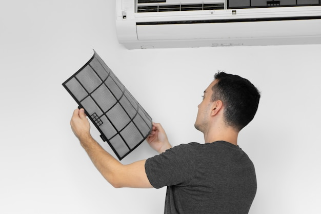 The guy cleans the filter of the home air conditioner from dust.