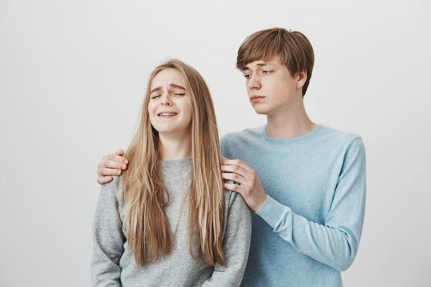 Il ragazzo conforta piangendo la ragazza, le tiene le spalle, esprime compassione