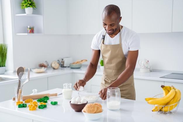 Парень кондитер делает свежий мягкий хлеб, замешивая муку, яйца кулинарные в современном интерьере кухни