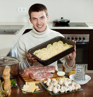 Guy cooking french-style meat in kitchen